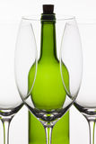 Three empty glasses of wine and green bottle Royalty Free Stock Photos