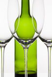 Three empty glasses of wine and green bottle Stock Image