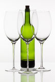 Three empty glasses of wine and green bottle Royalty Free Stock Photo