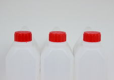 Three empty jerrycans of white plastic with red lids Stock Images
