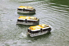 Three empty passengers transport vessels. With yellow roofs swing on water waves Royalty Free Stock Photography