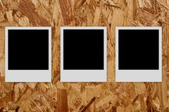 Three empty photo frames  on wood background Stock Images
