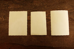 Three empty photographs on a brown wooden background Royalty Free Stock Image