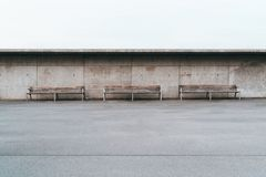 Three empty street outdoor benches with a concrete wall behind. Wide-angle minimalist shot of three wooden benches with metal legs standing in front of a grunge stock images