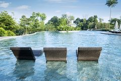 Three empty sun loungers. Image of three empty sun loungers in the swimming pool middle royalty free stock image