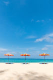Three empty sunbeds and beach parasol sunshades on sand beach Stock Image