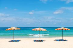 Three empty sunbeds and beach parasol sunshades on sand beach Royalty Free Stock Photo