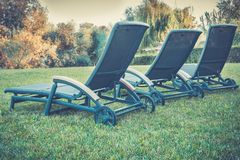 Three empty wheeled chaise lounges royalty free stock images