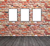 Three empty white frames on a brick wall Royalty Free Stock Images
