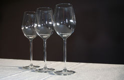 Three Empty Wine Glasses. In a row on a tablecloth with a black background Royalty Free Stock Photography