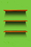 Three empty wooden shelves on the green wall Stock Photo
