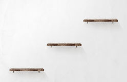 Three empty wooden shelves on the wall Stock Photo