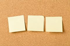 Three empty yellow sticky paper memo notes on cork board royalty free stock image