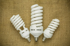 Three energy saving fluorescent lamp on the sackcloth background Royalty Free Stock Image