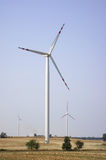 Three energy wind turbines. On field stock photography