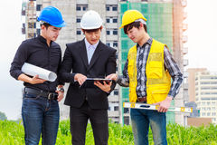 Three engineers checking plans with documents at construction si Royalty Free Stock Photography