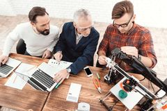 Three engineers sit at the table. Two work for computers, while the third configures a 3d printer. stock image