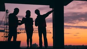 Three engineers work on a construction site on a sunset background. Construction workers at modern construction site. Three engineers work on a construction stock video