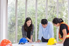 Three engineers working meeting room at the office. Three workers are talking construction plan. Electricians carpenter or. Technical operaters and Labourers or stock image