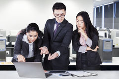 Three entrepreneurs discuss in the office Royalty Free Stock Image
