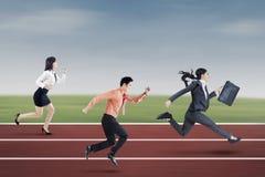 Three entrepreneurs running on the track Royalty Free Stock Image