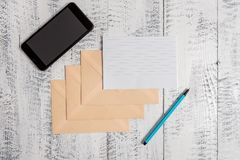 Three closed rectangular colored envelopes ruled paper sheet smartphone marker lying wooden retro vintage old rustic stock photos