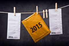 Three Envelopes with year numbers on clothes rope. Three Postal mail Envelopes with year numbers 2014, 2015 and 2016 hanging on rope attached with clothes pins Stock Photos