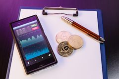 New ethereum mobile trading app. Three Ethereum ETH physical golden and shiny coins among with a clipboard with blank paper sheets, a pen and a mobile phone royalty free stock images