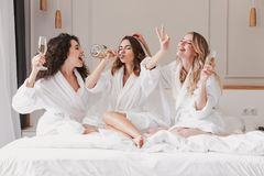 Three european young women 20s having fun at hen party and drink. Ing champagne in posh apartment or hotel room while bride trying on wedding veil stock photography