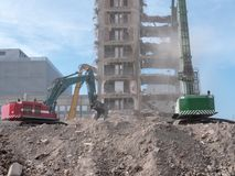Three excavators are busy demolishing an old company building royalty free stock images