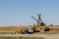 Three excavators dragline one bulldozer and one dismantled excavator stock image