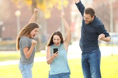 Three excited friends jumping checking smart phone in a park royalty free stock images