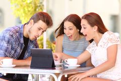 Three excited friends watching tablet content. Sitting in a coffee shop stock photos