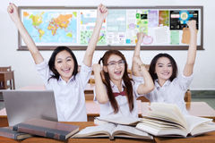 Three excited schoolgirls raise hands in the class Royalty Free Stock Photo