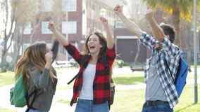 Excited students jumping celebrating good news. Three excited students jumping celebrating good news in a park stock footage