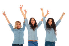 Three excited young casual women with hands in the air Stock Images