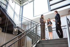 Three executives standing on a staircase Royalty Free Stock Image