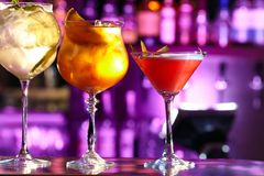 Three exotic cocktails in beautiful glasses. Three exotic cocktails in beautiful glasses are red, yellow and white. In a bar with a beautiful backlight royalty free stock images