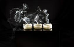 Three extinguished candles. Smoke. Stock Photo