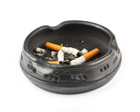 Three Extinguished Cigarettes in a Black Ashtray. Isolated on a white background stock photography