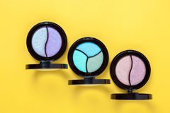 Three Eye shadows pallets and applicators on yellow background. royalty free stock photos