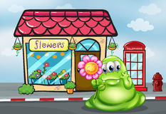 A three-eyed green monster holding a flower in front of the flow Stock Images