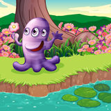 A three-eyed violet monster at the riverbank Stock Photos