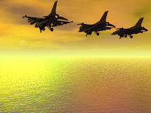 Three F-16 Fighter Jets. Fly low over the ocean with undercarriage down  towards a sunset Royalty Free Stock Photos