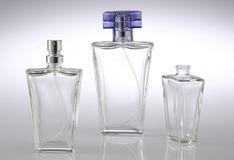 Three Fancy Perfume Bottles. Three clear fancy perfume or cologne bottles on white-gray reflective background Stock Image