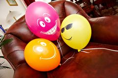 Three fanny balloons on brown chair Stock Photos