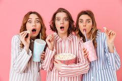 Three fascinating young girls 20s in colorful homewear eating po. P corn during watching thrilling and exciting movie at home party isolated over pink background stock photo