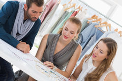 Three fashion designers discussing designs Royalty Free Stock Photography