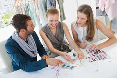 Three fashion designers discussing designs Stock Photography