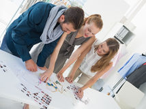 Three fashion designers discussing designs Royalty Free Stock Image